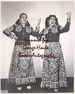 Two women in long shirts, singing.